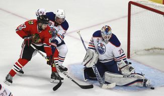 Edmonton Oilers goalie Cam Talbot (33) stops a shot by Chicago Blackhawks center Tanner Kero (67) as Oilers defenseman Andrej Sekera (2) pressures during the second period of an NHL hockey game Saturday, Feb. 18, 2017, in Chicago. (AP Photo/Jeff Haynes)