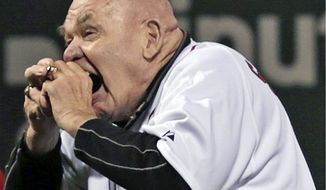 "FILE - In this Sept. 21, 2012, file photo, former professional wrestler George ""The Animal"" Steele bites the baseball before throwing out the ceremonial first pitch before a baseball game between the Baltimore Orioles and Boston Red Sox at Fenway Park in Boston. WWE Hall of Fame member George ""The Animal"" Steele, whose given name was Jim Myers, has died at age 79, the WWE announced Friday, Feb. 17, 2017. (AP Photo/Charles Krupa, File)"