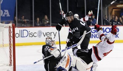 New Jersey Devils left wing Miles Wood (44) celebrates after scoring a goal as New York Islanders goalie Jean-Francois Berube (30) and New York Islanders defenseman Calvin de Haan (44) react to Wood's goal during the first period of an NHL hockey game, Sunday, Feb. 19, 2017, in New York, (AP Photo/Kathy Willens)