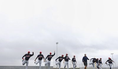 As storm clouds move in, Cleveland Indians position players run through their exercises at the Indians baseball spring training facility, Sunday, Feb. 19, 2017, in Goodyear, Ariz. (AP Photo/Ross D. Franklin)
