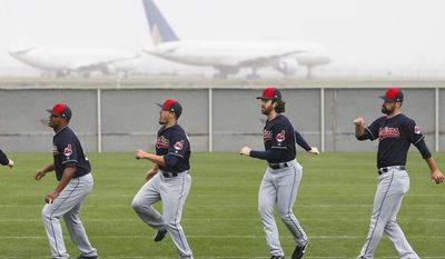As rain showers move through the area, Cleveland Indians pitchers Perci Garner, left, Shawn Morimando, second from left, TIm Cooney, second from right, and Adam Plutko, right, run through their exercises at the Indians baseball spring training facility, Sunday, Feb. 19, 2017, in Goodyear, Ariz. (AP Photo/Ross D. Franklin)