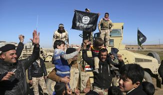 FILE -- In this Jan. 24, 2017 file photo, Iraqi Army soldiers celebrate with residents of liberated neighborhoods as they hold upside down a flag of the Islamic State group, in the eastern side of Mosul, Iraq. The U.N. and several aid organizations say an estimated 750,000 civilians are still living under Islamic State rule in Mosul despite recent advances by Iraqi forces. Lise Grande, the U.N. Humanitarian Coordinator for Iraq, said in a statement Tuesday that the cost of food and basic goods is soaring, water and electricity are intermittent and that some residents are forced to burn furniture to keep warm. (AP Photo/Khalid Mohammed, File)