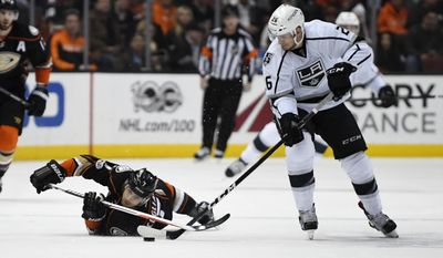 Anaheim Ducks left wing Andrew Cogliano, left, falls as Los Angeles Kings center Nic Dowd takes the puck during the first period of an NHL hockey game Sunday, Feb. 19, 2017, in Anaheim, Calif. (AP Photo/Mark J. Terrill)