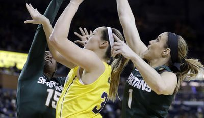 Michigan State forward Victoria Gaines (15) and guard Tori Jankoska (1) attempt to block a shot by Michigan center Hallie Thome (30) during the first half of an NCAA college basketball game, Sunday, Feb. 19, 2017, in Ann Arbor, Mich. (AP Photo/Carlos Osorio)