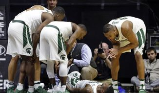 Michigan State players surround guard Eron Harris (14) after he was injured in the second half of an NCAA college basketball game against Purdue in West Lafayette, Ind., Saturday, Feb. 18, 2017. Purdue defeated Michigan State 80-63. (AP Photo/Michael Conroy)