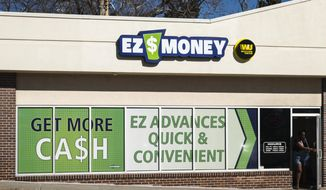 In this Friday, Feb. 17, 2017 photo, an unidentified person leaves the EZ Money Check Cashing storefront in Omaha, Neb. About 80 Nebraska businesses offer payday loans, according to the state Department of Banking and Finance. Several of these businesses, including EZ Money, have multiple storefronts. A Nebraska legislative committee on Tuesday, Feb. 21, 2017, will hear two vastly different approaches to regulating the payday lending industry. (AP Photo/Nati Harnik)
