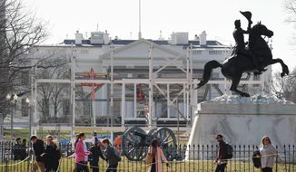 In this photo taken Feb. 17, 2017, pedestrians walk through Lafayette Park, across from the White House in Washington, as work continues with the dismantling of the presidential inauguration reviewing stand. (AP Photo/Pablo Martinez Monsivais)