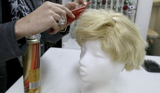 Manuela Plank owner of a costume rental shop fashioning normal blond hairpieces into Trump wigs in Pfaffstaetten, Austria, Monday, Feb. 20, 2017. Just about everyone wants to be Donald Trump this carnival season in Austria _ so much so that some costume rentals are out of stock of wigs miming the U.S. president's signature hairstyle. (AP Photo/Ronald Zak)