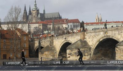 Switzerland's tennis player Roger Federer, right, returns a ball to Czech Republic's Tomas Berdych, left, during an exhibition match on Vltava river in Prague, Czech Republic, Monday, Feb. 20, 2017. Federer arrived in Prague to promote the Laver Cup, a tournament that will be held in Prague on Sept. 22-24, 2017, pitting six top European players against their counterparts from the rest of the world. The Charles Bridge and he Prague Castle are in the background. (AP Photo/Petr David Josek)