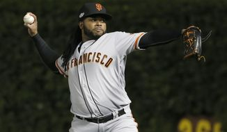 FILE - In this Oct. 7, 2016, file photo, San Francisco Giants starting pitcher Johnny Cueto warms up before Game 1 of baseball's National League Division Series against the Chicago Cubs in Chicago. Cueto remains in his native Dominican Republic helping his ailing father a week after pitchers and catchers reported to spring training, and the Giants planned to reach out to him to determine how he is doing and whether he thinks he will be ready to pitch for his country in the World Baseball Classic. (AP Photo/Nam Y. Huh, File)