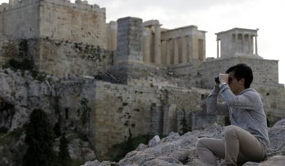 A tourist uses his binoculars as the ancient Acropolis hill is seen in the background during a 24-hour strike by archaeological guards demanding unpaid wages and the recruitment of additional employees in Athens, Monday, Feb. 20, 2017. Greece has been struggling for months to conclude negotiations with its creditors on spending cuts and reforms demanded by European creditors and the International Monetary Fund as part of its third bailout program. (AP Photo/Thanassis Stavrakis)