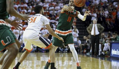 Miami guard Bruce Brown (11) passes around Virginia guard Darius Thompson (51) during the first half of an NCAA college basketball game Monday, Feb. 20, 2017, in Charlottesville, Va. (AP Photo/Ryan M. Kelly)