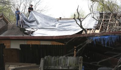 Mickey Opielski, left, and his brother, Jason Opielski, work on a duplex roof after severe weather moved through the Camelot subdivision of Northeast Bexar County, Texas, Monday, Feb. 20, 2017. Severe storms pushed at least two tornadoes through parts of San Antonio, damaging dozens of homes.  (Jerry Lara/The San Antonio Express-News via AP)