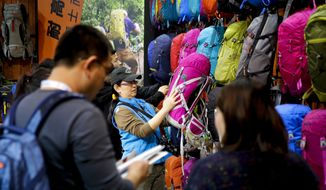 "In this Thursday, Feb. 16, 2017 photo, visitors look at Chinese brand outdoor backpacks on display at the International Trade Show for Mountain and Winter Technologies in Beijing. Chinese Premier Li Keqiang, China's No. 2 leader, expressed hope that disputes with U.S. President Donald Trump's government can be settled amicably and warned a ""trade war would benefit nobody."" (AP Photo/Andy Wong)"