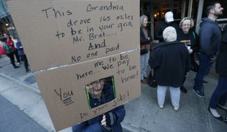 Michelle Harrington, of Midlothian Va., peers from behind a grill in her homemade sign as she and other constituents of Congressman Dave Brat, R-Va., stand in line for a town hall meeting with the congressman in Blackstone, Va., Tuesday, Feb. 21, 2017. Brat complained that he had women in his grill at town hall meetings. (AP Photo/Steve Helber)