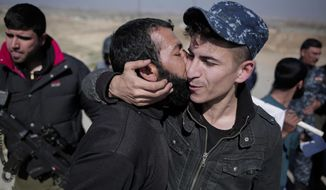 A civilian kisses a federal police officer after escaping Islamic State territory in the town of Abu Saif, Tuesday, Feb. 21, 2017.  Iraqi forces advanced into the southern outskirts of Mosul in a push to drive Islamic State militants from the city's western half, as the visiting U.S. defense secretary met with officials to discuss the fight against the extremists.(AP Photo/Bram Janssen)