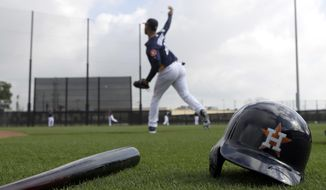 Houston Astros third baseman Yuli Gurriel throws during a spring training baseball workout Sunday, Feb. 19, 2017, in West Palm Beach, Fla. (AP Photo/David J. Phillip)
