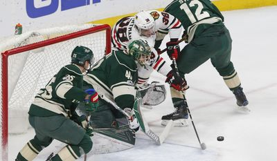 Chicago Blackhawks' Ryan Hartman, second from right, tries to work between Minnesota Wild's Eric Staal, right, and goalie Devan Dubnyk during the first period of an NHL hockey game, Tuesday, Feb. 21, 2017, in St. Paul, Minn. (AP Photo/Jim Mone)