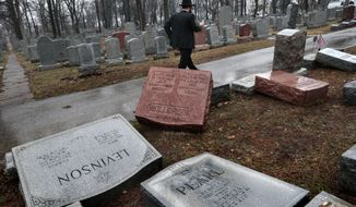 """Rabbi Hershey Novack of the Chabad center walks through Chesed Shel Emeth Cemetery in University City on Tuesday, Feb. 21, 2017, where almost 200 gravestones were vandalized over the weekend. """"People who are Jewish are shocked and angry,"""" Novack said. (Robert Cohen/St. Louis Post-Dispatch via AP)"""
