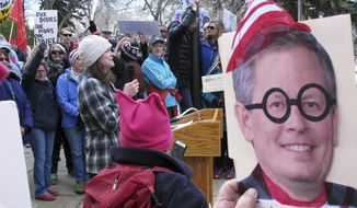 Katherine Haque-Hausrath, with a microphone, , one of the organizers for a rally, addresses a crowd outside the Montana Capitol in Helena on Tuesday, Feb. 21, 2017. Hundreds of protesters who were upset that U.S. Sen. Steve Daines wasn't planning a town hall this week decided to bring one to him instead outside of the Montana Capitol, where Daines was scheduled to address the state Legislature on Tuesday. (AP Photo/Matt Volz)