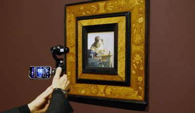 """""""The Lacemaker"""", a 1669-1670 oil painting on canvas by Johannes Vermeer is presented to the press during the opening of the exhibition entitled """"Vermeer and the Masters of Genre Painting,"""" at Louvre Museum, in Paris, Tuesday, Feb. 21, 2017. The Louvre has inaugurated a major exhibit of old master Johannes Vermeer, presenting 12 of the Flemish painter's oil canvasses including The Milkmaid. (AP Photo/Francois Mori)"""