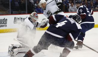 Los Angeles Kings center Trevor Lewis, back center, scores a goal past Colorado Avalanche goalie Calvin Pickard, back left, as Colorado Avalanche defensemen Tyson Barrie, front, and Fedor Tyutin, of Russia, cover in the second period of an NHL hockey game, Tuesday, Feb. 21, 2017, in Denver. (AP Photo/David Zalubowski)