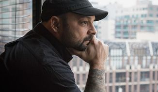 In this Jan. 9, 2017, photo, Christian Picciolini, founder of the group Life After Hate, poses for a photograph in his Chicago home. Picciolini, a former skinhead, is an activist combatting what many see as a surge in white nationalism across the United States. He's doing it by helping members quit groups including the Ku Klux Klan and skinhead organizations. (AP Photo/Teresa Crawford)