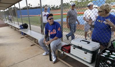 New York Mets' Wilmer Flores (4) talks with a fan during a spring training baseball workout Wednesday, Feb. 15, 2017, in Port St. Lucie, Fla. (AP Photo/David J. Phillip)