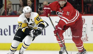 Pittsburgh Penguins' Sidney Crosby (87) and Carolina Hurricanes' Jordan Staal (11) chase the puck during the second period of an NHL hockey game in Raleigh, N.C., Tuesday, Feb. 21, 2017. (AP Photo/Gerry Broome)