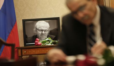 A picture of Vitaly Churkin, Russia's ambassador to the United Nations, is displayed while people sign condolences books at the Russian Mission to the U.N. in New York, Tuesday, Feb. 21, 2017. The city medical examiner was expected to perform an autopsy Tuesday on Russia's ambassador to the U.N., who died a day earlier after falling ill at his office at Russia's U.N. mission. (AP Photo/Seth Wenig)