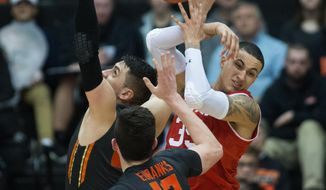 Oregon State's Gligorije Rakocevic, left, and Drew Eubanks (12) fight Utah's Kyle Kuzma for a loose ball during the second half of an NCAA college basketball game in Corvallis, Ore., Sunday, Feb. 19, 2017. Oregon State won 68-67 for their first win in a Pac-12 Conference game this year. (AP Photo/Timothy J. Gonzalez)