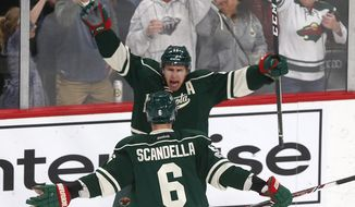 Minnesota Wild's Zach Parise, top, celebrates his goal off Chicago Blackhawks goalie Corey Crawford during the third period of an NHL hockey game, Tuesday, Feb. 21, 2017, in St. Paul, Minn. The Blackhawks won 5-3. (AP Photo/Jim Mone)