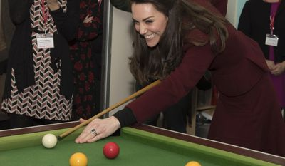 Britain's Princess Kate Duchess of Cambridge has a go at playing pool during her visit to Action for Children project MIST, a child and adolescent mental health project which works specifically with children who are living in care, in Torfaen, Wales, Wednesday Feb. 22, 2017.  This is the first engagement for Princess Kate with Action for Children since becoming its Patron in December, following on from Her Majesty The Queen. (Paul Edwards/pool via AP)