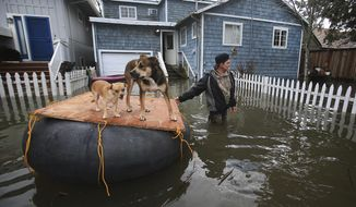 James Fipps takes his dogs for a walk on a makeshift raft as Clear Lake continues to inundate homes with flooding, Tuesday Feb. 21, 2017, in Lakeport, Calif.  (Kent Porter/The Press Democrat via AP)