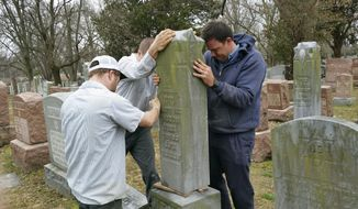 Rosenbloom Monument Co. workers from left, Derek Doolin, Nathan Fohne, and Philip Weiss hoist a headstone at the Chesed Shel Emeth Cemetery in University City, Mo., where over 150 headstones were tipped over. No arrests have been made. The cemetery is getting a show of support from cleanup volunteers, well-wishers and financial contributors from across many faiths. (AP Photo/Jim Salter)