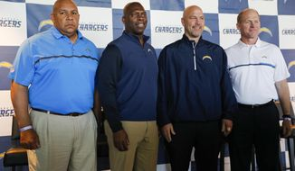 Los Angeles Chargers special team coordinator George Stewart, from left, head coach Anthony Lynn, defensive coordinator Gus Bradley and offensive coordinator Ken Whisenhunt pose for photos after a news conference Wednesday, Feb. 22, 2017, in Carson, Calif. (AP Photo/Jae C. Hong)
