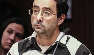 FILE - In this Friday, Feb. 17, 2017, file photo, Dr. Larry Nassar listens to testimony of a witness during a preliminary hearing, in Lansing, Mich. The former sports doctor at Michigan State University who specialized in treating gymnasts has been charged with sexual assault. Dr. Nassar was charged Wednesday, Feb. 22,  in two Michigan counties. Online records show he's facing nine charges in Ingham county, including first-degree criminal sexual conduct against a victim under age 13. Nassar had a clinic at Michigan State, where he treated members of the gymnastics team and younger regional gymnasts. (Robert Killips/Lansing State Journal via AP, File)