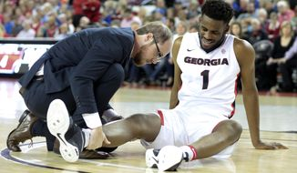 """FILE - In this Feb. 18, 2017 file photo, Georgia forward Yante Maten (1) has his knee looked at by the Georgia trainer during an NCAA men's basketball against Kentucky in Athens, Ga. A knee sprain is expected to keep Georgia leading scorer Yante Maten out for the remainder of the regular season, and coach Mark Fox says the Bulldogs must """"reinvent what we do"""" as they play Alabama on Thursday, Feb. 23 and LSU on Saturday. (John RoarkAthens Banner-Herald via AP)"""