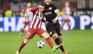 Atletico's Kevin Gameiro, left, and Leverkusen's Omer Toprak challenge for the ball during the Champions League round of 16 first leg soccer match between Bayer Leverkusen and Atletico Madrid in Leverkusen, Germany, Tuesday, Feb. 21, 2017. (AP Photo/Martin Meissner)