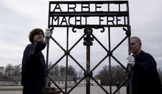 """Employees of a transport company carry the gate with the writing """"Arbeit macht frei"""" (Work Sets you Free) at the memorial of the former  Nazi concentration camp in Dachau, Germany, Wednesday, Feb. 22, 2017.  The gate  was stolen in 2014 and reappeared in November 2016 near the city of Bergen in Norway.  (Sven Hoppe/dpa via AP)"""