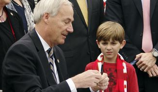 Murphy Wardlaw watches as Gov. Asa Hutchinson signs a bill on the field at War Memorial Stadium on Wednesday, Feb. 22, 2017, in Little Rock placing the stadium under the control of the state Parks and Tourism Department. Hutchinson said that he would like to see the Arkansas Razorbacks continue to play football games in the stadium after a current contract expires in 2018. (AP Photo/Kelly P. Kissel)