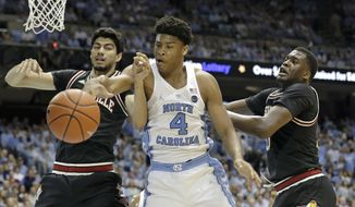 North Carolina's Isaiah Hicks (4) struggle for possession of the ball with Louisville's Anas Mahmoud, left, and Jaylen Johnson during the first half of an NCAA college basketball game in Chapel Hill, N.C., Wednesday, Feb. 22, 2017. (AP Photo/Gerry Broome)