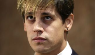 Milo Yiannopoulos listens during a news conference in New York, Tuesday, Feb. 21, 2017. Yiannopoulos has resigned as editor of Breitbart Tech after coming under fire from other conservatives over comments on sexual relationships between boys and older men. (AP Photo/Seth Wenig)