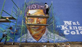 In this Friday, Feb. 17, 2017 photo, artists Sunny Paulk, left, and Corey Spearman put the finishing touches on a mural of Nat King Cole on the side of a building in downtown Montgomery, Ala. The Nat King Cole mural, located on Maxwell Boulevard overlooking downtown, is the second public art project commissioned by the Public Art Commission. (Mickey Welsh/The Montgomery Advertiser via AP)