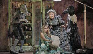 """This Jan. 24, 2017 image released by the Metropolitan Opera shows mezzo-soprano Jamie Barton, as the witch Jezibaba, standing, with soprano Kristine Opolais, as the water nymph Rusalka, in Dvorak's opera """"Rusalka."""" It will be broadcast live in HD from the Metropolitan Opera on Feb. 25. (Ken Howard/Metropolitan Opera via AP)"""
