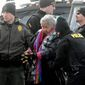 An elderly woman is escorted to a transport van after being arrested by law enforcement at the Oceti Sakowin camp as part of the final sweep of the Dakota Access pipeline protesters on Thursday in Morton County near Cannon Ball, North Dakota. (Associated Press photographs)
