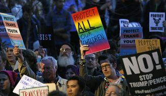 Protesters hold signs during a rally in support of transgender youth, Thursday, Feb. 23, 2017, at the Stonewall National Monument in New York. They were demonstrating against President Donald Trump's decision to roll back a federal rule saying public schools had to allow transgender students to use the bathrooms and locker rooms of their chosen gender identity. The rule had already been blocked from enforcement, but transgender advocates view the Trump administration action as a step back for transgender rights. (AP Photo/Kathy Willens)