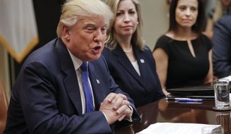 President Donald Trump speaks during a meeting on domestic and international human trafficking, Thursday, Feb. 23, 2017, in the Roosevelt Room of the White House in Washington. With Trump are Michelle DeLaune, center, National Center for Missing and Exploited Children, and Dina Powell, right, White House Senior Counselor for Economic Initiatives. (AP Photo/Pablo Martinez Monsivais)