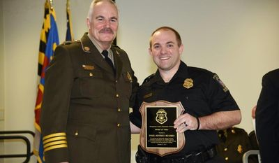 In this Feb. 22, 2017 photo provided by Montgomery County Police, Officer Jeff Hughes, right, poses for a photo with the Medal of Valor award with Chief Tom Manger in Gaithersburg, Md. Hughes, who was the first to respond to a gas explosion and fire that killed seven people last year has received his department's highest honor. (Montgomery County Police via AP)