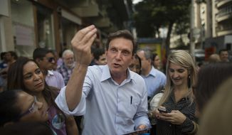 In this Sept. 29, 2014 photo, Marcelo Crivella, bishop of the Universal Church of the Kingdom of God, who was running for governor of Rio de Janeiro state, campaigns at Copacabana, Rio de Janeiro, Brazil. While campaigning last year to be Rio de Janeiro's mayor, Crivella, a Pentecostal pastor from one of Brazil's most powerful evangelical churches, repeatedly argued that his faith would not get in the way of governing the nation's most famous city. (AP Photo/Leo Correa)